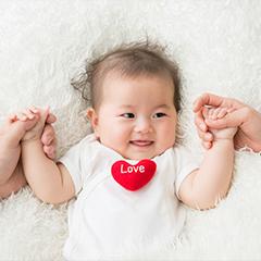 両手を握られている赤ちゃん